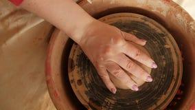 Επίπεδος βάλτε την άποψη άνωθεν των θηλυκών χεριών που κολλούν τον ακατέργαστο άργιλο στη ρόδα αγγειοπλαστικής απόθεμα βίντεο