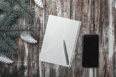 Επίπεδος βάλτε την άποψη του φύλλου στο κέντρο της χαριτωμένης διακόσμησης, των κώνων και του τηλεφώνου Χριστουγέννων Υψηλή γωνία Στοκ Εικόνα