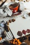 Επίπεδος βάλτε την άποψη των φύλλων φθινοπώρου και του κατασκευασμένου πουλόβερ ταρτάν στο ξύλινο υπόβαθρο με το φλυτζάνι του τσα στοκ εικόνα με δικαίωμα ελεύθερης χρήσης