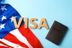 Επίπεδος βάλτε τη σύνθεση με τη ΘΕΩΡΗΣΗ, το διαβατήριο και τη σημαία λέξης των ΗΠΑ στοκ φωτογραφία