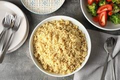Επίπεδος βάλτε τη σύνθεση με μαγειρευμένο quinoa στο πιάτο στοκ φωτογραφίες