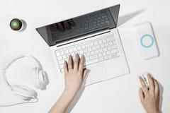 Επίπεδος βάλτε τη σύνθεση με τα θηλυκά χέρια δακτυλογραφώντας στο lap-top Άσπρο γραφείο με το lap-top, τον κάκτο, τα ακουστικά μο Στοκ φωτογραφία με δικαίωμα ελεύθερης χρήσης