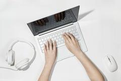 Επίπεδος βάλτε τη σύνθεση με τα θηλυκά χέρια δακτυλογραφώντας στο lap-top Άσπρο γραφείο με το lap-top, τα ακουστικά μουσικής και  Στοκ Φωτογραφίες