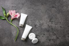 Επίπεδος βάλτε τη σύνθεση με τα καλλυντικά και το λουλούδι προσοχής σωμάτων Στοκ Εικόνες