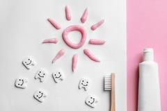 Επίπεδος βάλτε τη σύνθεση με τα μικρές πλαστικές δόντια και την κόλλα στοκ εικόνα