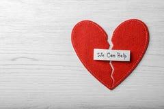 Επίπεδος βάλτε τη σύνθεση με τα μισά αισθητής της κόκκινο καρδιάς, σημείωση που ΜΠΟΡΟΥΜΕ ΝΑ ΒΟΗΘΗΣΟΥΜΕ και διάστημα για το κείμεν στοκ εικόνες
