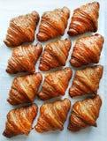 Επίπεδος βάλτε τη σύνθεση με τα νόστιμα croissants στο διαμορφωμένο υπόβαθρο Στοκ Εικόνες