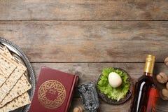 Επίπεδος βάλτε τη σύνθεση με τα συμβολικά στοιχεία Passover Pesach στο ξύλινο υπόβαθρο στοκ φωτογραφίες