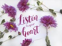 Επίπεδος βάλτε τη σύνθεση με τα chrisanthemums και η γράφοντας κάρτα ` ακούει την καρδιά σας ` στοκ εικόνες