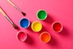 Επίπεδος βάλτε τη σύνθεση με τις βούρτσες γκουας και χρωμάτων στο ρόδινο υπόβαθρο στοκ φωτογραφία με δικαίωμα ελεύθερης χρήσης