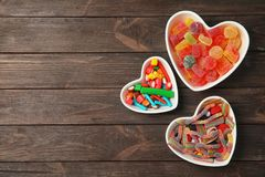 Επίπεδος βάλτε τη σύνθεση με τις διαφορετικές yummy καραμέλες διαμορφωμένα στα καρδιά κύπελλα και το διάστημα για το κείμενο στοκ εικόνες