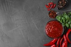 Επίπεδος βάλτε τη σύνθεση με το κύπελλο της σάλτσας και των συστατικών τσίλι στον γκρίζο πίνακα στοκ φωτογραφία