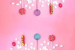 Επίπεδος βάλτε τη σύνθεση με το πλαίσιο των lollipops και marshmallows και το διάστημα για το κείμενο στο ρόδινο υπόβαθρο στοκ εικόνες με δικαίωμα ελεύθερης χρήσης