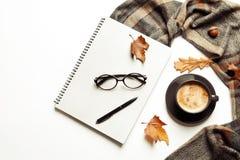 Επίπεδος βάλτε τη σύνθεση με το σημειωματάριο, το φλιτζάνι του καφέ και το θερμό κάλυμμα στο άσπρο υπόβαθρο στοκ εικόνα