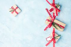 Επίπεδος βάλτε τη τοπ άποψη τέσσερα κιβώτια δώρων Χριστουγέννων στο έγγραφο τεχνών με τις κόκκινες κορδέλλες σε ανοικτό μπλε Στοκ Εικόνες