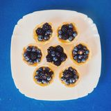 Επίπεδος βάλτε τη φωτογραφία των tattletales με το βακκίνιο και το βατόμουρο στον μπλε πίνακα Στοκ Εικόνες