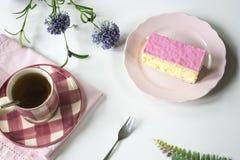 Επίπεδος βάλτε τη χαρακτηριστική ολλανδική γλυκιά ρόδινη βερνικωμένη ζύμη tompouce στο ρόδινο πιάτο Με το φλυτζάνι του τσαγιού στοκ φωτογραφίες