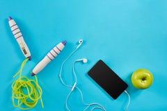 Επίπεδος βάλτε τον πυροβολισμό του αθλητικού εξοπλισμού Apple, σχοινί άλματος, ακουστικά και τηλέφωνο στο μπλε υπόβαθρο Στοκ Εικόνες