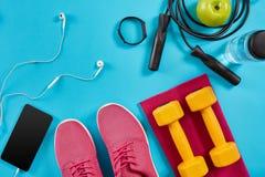 Επίπεδος βάλτε τον πυροβολισμό των πάνινων παπουτσιών, του σχοινιού άλματος, των αλτήρων και του smartphone στο μπλε υπόβαθρο Στοκ φωτογραφίες με δικαίωμα ελεύθερης χρήσης
