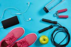 Επίπεδος βάλτε τον πυροβολισμό των πάνινων παπουτσιών, του σχοινιού άλματος, των αλτήρων και του smartphone στο μπλε υπόβαθρο Στοκ φωτογραφία με δικαίωμα ελεύθερης χρήσης