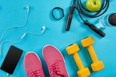 Επίπεδος βάλτε τον πυροβολισμό των πάνινων παπουτσιών, του σχοινιού άλματος, των αλτήρων και του smartphone στο μπλε υπόβαθρο Στοκ εικόνες με δικαίωμα ελεύθερης χρήσης