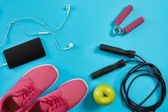 Επίπεδος βάλτε τον πυροβολισμό των πάνινων παπουτσιών, του σχοινιού άλματος, των αλτήρων και του smartphone στο μπλε υπόβαθρο Στοκ Φωτογραφίες