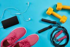 Επίπεδος βάλτε τον πυροβολισμό των πάνινων παπουτσιών, του σχοινιού άλματος, των αλτήρων και του smartphone στο μπλε υπόβαθρο Στοκ εικόνα με δικαίωμα ελεύθερης χρήσης
