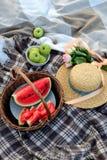 Επίπεδος-βάλτε του καλαθιού με τις φέτες του καρπουζιού, ένα κύπελλο με τα πράσινα μήλα, μια ανθοδέσμη των ρόδινων τριαντάφυλλων, στοκ εικόνες