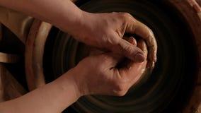 Επίπεδος βάλτε το θηλυκό χέρι άποψης άνωθεν που παίρνει τον άργιλο για να εργαστεί στη ρόδα αγγειοπλαστικής απόθεμα βίντεο