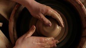 Επίπεδος βάλτε το θηλυκό χέρι άποψης άνωθεν που παίρνει τον άργιλο για να εργαστεί στη ρόδα αγγειοπλαστικής φιλμ μικρού μήκους