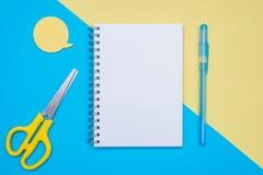 Επίπεδος βάλτε το σχέδιο με το κενό στο βιβλίο σημειώσεων μπλε κίτρινος ανασκόπηση&sig Φυσαλίδα για τη μάνδρα και το ψαλίδι κειμέ Στοκ Εικόνες