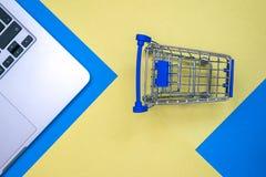 Επίπεδος βάλτε το σχέδιο με το lap-top και το καροτσάκι μπλε κίτρινος ανασκόπησης Αγοράστε τη σε απευθείας σύνδεση έννοια Στοκ Φωτογραφία