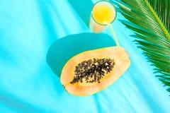 Επίπεδος βάλτε το ψηλό γυαλί σύνθεσης με το φρέσκο τροπικό Papaya χυμού φρούτων διχοτομημένο φύλλο φοινικών στο μπλε υπόβαθρο Σκλ στοκ φωτογραφίες