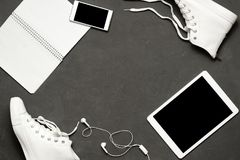 Επίπεδος βάλτε των άσπρων πάνινων παπουτσιών μόδας στο μαύρο υπόβαθρο με το τηλέφωνο, ακουστικά, ταμπλέτα, βιβλίο αντιγράφων Στοκ εικόνα με δικαίωμα ελεύθερης χρήσης