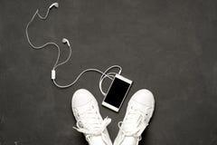 Επίπεδος βάλτε των άσπρων πάνινων παπουτσιών στο μαύρο υπόβαθρο με το τηλέφωνο και τα ακουστικά Στοκ Φωτογραφία