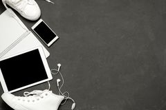 Επίπεδος βάλτε των άσπρων πάνινων παπουτσιών στο μαύρο υπόβαθρο με το τηλέφωνο, ακουστικά, ταμπλέτα, βιβλίο αντιγράφων Στοκ Εικόνα