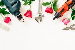 Επίπεδος βάλτε των λειτουργώντας εργαλείων και των τριαντάφυλλων κατασκευής στο λευκό grunge Στοκ φωτογραφία με δικαίωμα ελεύθερης χρήσης