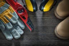 Επίπεδο κατασκευής μποτών γαντιών ασφάλειας καλυμμάτων αυτιών στον ξύλινο πίνακα Στοκ εικόνες με δικαίωμα ελεύθερης χρήσης