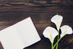Επίπεδος βάλτε τα άσπρα λουλούδια και το ημερολόγιο στο ξύλινο υπόβαθρο, τοπ άποψη Χλεύη επάνω Στοκ Φωτογραφίες