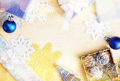 Επίπεδος βάλτε τα δώρα, τα παιχνίδια και snowflakes Χριστουγέννων στο ξύλο Στοκ Φωτογραφία