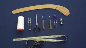 Επίπεδος βάλτε Το ύφασμα χρώματος, ψαλίδι, μια μπούκλα, κουμπιά, νήματα είναι ορατό φιλμ μικρού μήκους
