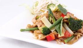 Επίπεδο noodle ρυζιού ανακατώνει τηγανισμένος με το ταϊλανδικούς χορτάρι και το βασιλικό. Στοκ Εικόνες
