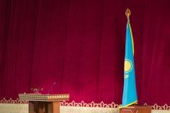 Επίσημες ειδήσεις του Καζάκου έννοιας Σημαία της Δημοκρατίας του Καζακστάν και το nightstand για τον ομιλητή σε ένα κόκκινο υπόβα στοκ φωτογραφία με δικαίωμα ελεύθερης χρήσης