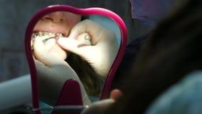 Επίσκεψη και διαβουλεύσεις με τον οδοντίατρο, εγκατάσταση των στηριγμάτων Το orthodontist λέει το σχέδιο θεραπείας, ο ασθενής φιλμ μικρού μήκους
