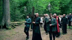 Επίσκοπος και παλαιός γκρίζος επικεφαλής φέρνοντας σταυρός ατόμων όπως το Ιησούς Χριστό Calvary φιλμ μικρού μήκους