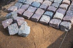 Επίστρωση κυβόλινθων - pavers πετρών γρανίτη στο αμμοχάλικο στοκ εικόνες