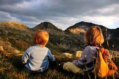 Επίτευξη της κορυφής, δύο παιδιά που προσέχει την αιχμή βουνών στοκ εικόνες