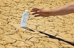 Επίτευξη το εμφιαλωμένο νερό ερήμων που γέρνουν για Στοκ φωτογραφίες με δικαίωμα ελεύθερης χρήσης