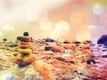 Επίδραση ταινιών Ισορροπημένη πυραμίδα πετρών στην ακροθαλασσιά, κύματα στο υπόβαθρο Ζωηρόχρωμες επίπεδες πέτρες για την περισυλλ Στοκ Φωτογραφία