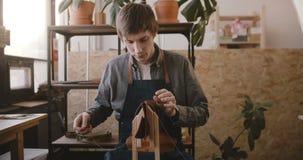 Επαγγελματικά αρσενικά χειροτεχνικά ράβοντας χειροποίητα αγαθά δέρματος στο saddler με τις βελόνες στο ελαφρύ σύγχρονο εργαστήριο φιλμ μικρού μήκους